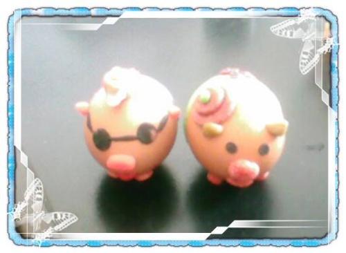 这是一对小福猪,猪屁股上都用橡皮泥贴了一个福字,可爱又吉祥.